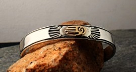 """Navajo Hand-Hammered Sterling Silver and 14 Karat Gold Accent Bracelet.  Healing Hand Design.  Medium-Sizing.   """"Each Piece tells a story of how the Native Peoples used to live, or meanings in their lives. Each piece is signed by the artist. Each piece is a collector's piece."""""""