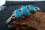 """Navajo 3-Stone Sterling Silver Bracelet.  Inlaid with Natural Turquoise Stones. 2/8"""" band width, 7/8"""" at widest point, 5/12"""" circumference, 2 1/2"""" diameter."""